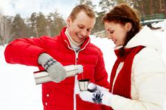 portrait of happy couple going to drink hot tea on winter day - stock photo