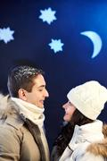 Stock Photo of portrait of happy couple looking at one another with moon and stars above their