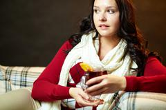 portrait of pretty female holding glass of hot tea while sitting on sofa - stock photo