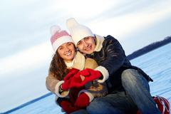 portrait of happy couple in warm clothes making heart by hands - stock photo