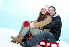 portrait of happy couple sitting on sledge under snowfall - stock photo