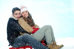 Portrait of happy couple sitting on sledge under snowfall and looking at camera Stock Photos