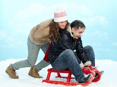 portrait of happy couple tobogganing during winter vacation - stock photo