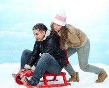 Portrait of happy couple tobogganing during winter vacation Stock Photos
