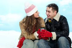 Portrait of amorous couple drinking hot tea on winter day Stock Photos