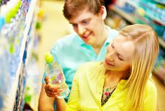 Image of happy couple choosing mineral water in supermarket Stock Photos