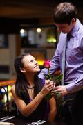 image of man giving a red rose to his girlfriend - stock photo