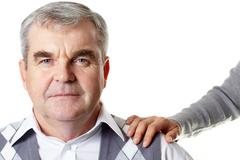 portrait of a senior man with a female hand on his shoulder - stock photo