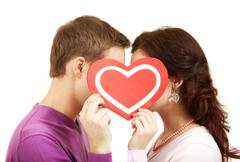 Two young people kissing behind a paper heart Stock Photos