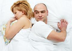 photo of dissatisfied husband looking his wife - stock photo