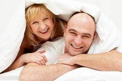 happy woman lying on the husband under blanket - stock photo