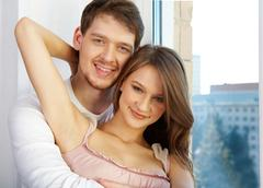 portrait of young woman with man looking at camera - stock photo