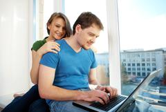 Photo of man typing on the laptop and woman behind Stock Photos