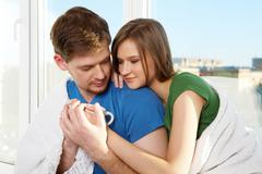 close-up of young man and woman touching cup together - stock photo