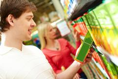 Portrait of happy man holding pack of juice in supermarket Stock Photos