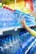 close-up of female holding plastic bottle of mineral water in a shop - stock photo