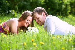happy woman with bunch of flowers and her boyfriend resting on green lawn in par - stock photo