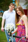 happy woman with bunch of flowers looking at camera with her boyfriend on backgr - stock photo