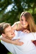 photo of happy girl embracing her boyfriend and looking at camera - stock photo