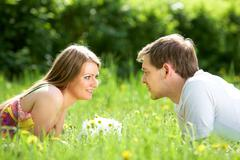 happy woman and her boyfriend resting on green lawn in park - stock photo