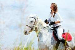 Image of happy female jockey on purebred horse outdoors Stock Photos