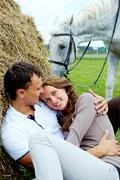 Photo of affectionate couple having rest on haystack Stock Photos