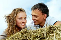 Photo of affectionate couple relaxing on haystack Stock Photos