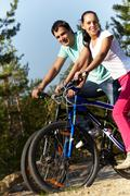 Portrait of a sporting couple on bicycles looking at camera and smiling Stock Photos