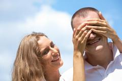 laughing female keeping her hands on male's eyes and looking at him - stock photo
