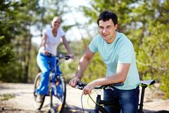 portrait of a handsome man with his bike against his girlfriend - stock photo