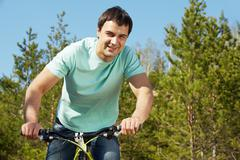 portrait of a handsome man riding a bike - stock photo
