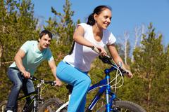 a young couple racing on bicycles - stock photo