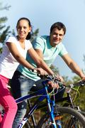 portrait of two young people on bikes - stock photo