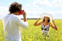 Image of young guy taking photos of pretty girl on yellow field at summer Stock Photos