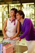 portrait of happy couple looking at something during shopping in the mall - stock photo