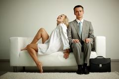 photo of serious man in suit sitting on sofa with seductive laughing woman near - stock photo