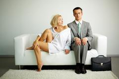 Photo of serious man sitting on sofa with seductive woman looking at him Stock Photos