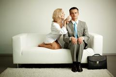 Photo of serious man sitting on sofa with seductive woman teasing him Stock Photos