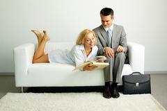 photo of smiling man sitting on sofa with happy woman lying near by and both loo - stock photo