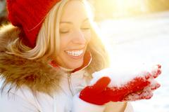 portrait of happy girl holding snow on palms with sunshine over her - stock photo