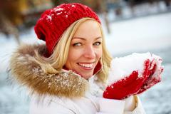 portrait of happy girl holding snow on palms and looking at camera - stock photo