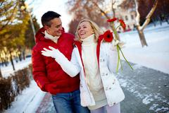 photo of happy man and pretty woman walking outdoor in winter - stock photo