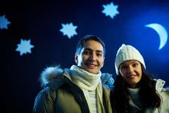 Stock Photo of portrait of happy couple looking at camera with moon and stars above their heads