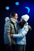 Stock Photo of portrait of happy couple looking at one another with moon and stars above
