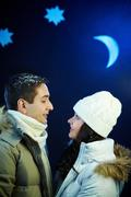 portrait of happy couple looking at one another with moon and stars above their - stock photo