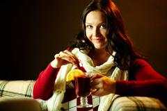 portrait of pretty female with tea looking at camera - stock photo