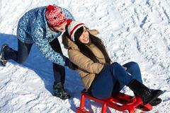Portrait of happy couple tobogganing in winter Stock Photos