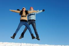 portrait of happy couple in warm clothes jumping and looking at camera - stock photo