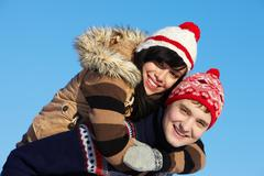 portrait of happy couple in warm clothes embracing and looking at camera - stock photo