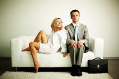 Photo of serious man sitting on sofa with happy seductive woman looking at him Stock Photos